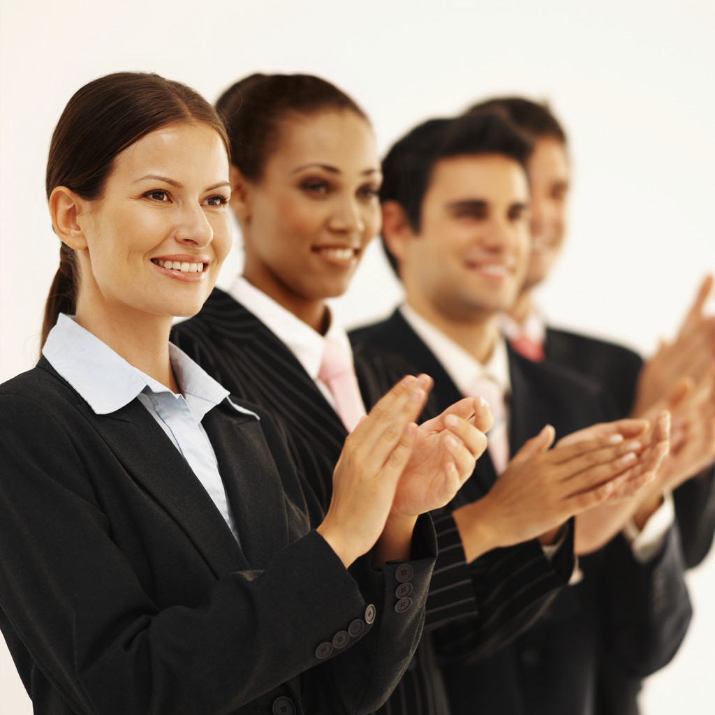 Close-up of four business executives standing in a line and applauding