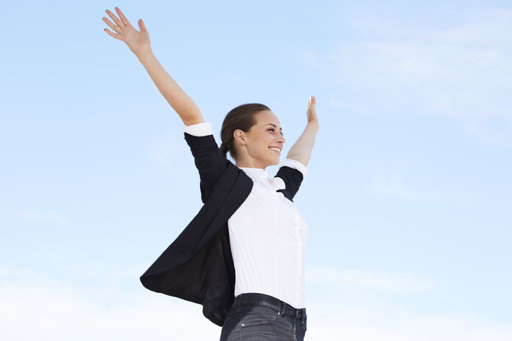 Young businesswoman with arms out against blue sky